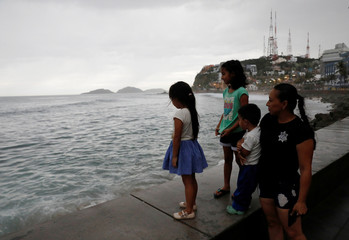 A family look at the sea along the Mazatlan boardwalk as Hurricane Willa approaches the Pacific beach resort