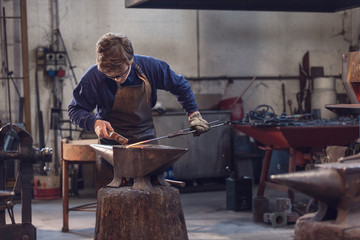 Young blacksmith working with red hot metal