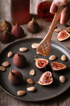 Drizzling honey on a plate of figs and marcona almonds.
