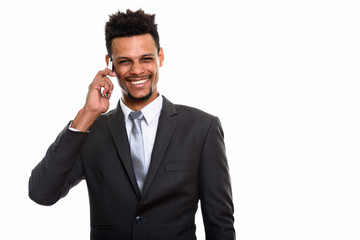 Young happy African businessman smiling while talking on mobile