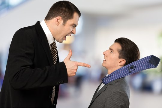 Businessman shouting orders at a worker