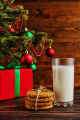 Milk, cookies and gifts under the Christmas tree. The concept of the arrival of Santa Claus.
