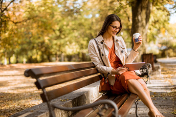 Young woman drinks coffee and using digital tablet in the park