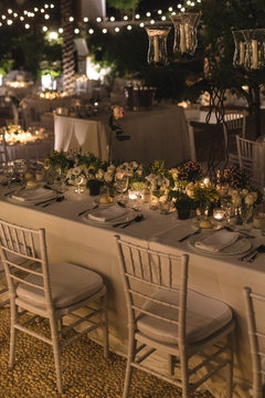 Floral arrangement in a decorated table for a wedding at night with candles