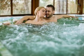 Loving couple relaxing in hot tub