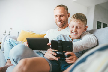 Father and son game players funs sit together at home on cozy sofa, using the tablet and gamepad