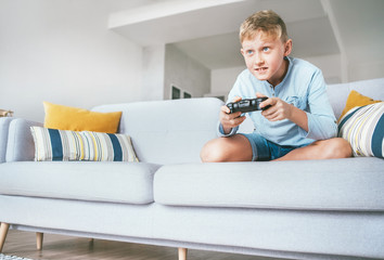 Preteen boy enthusiastically plays the game console
