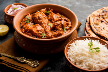 Murgh Makhani / Butter chicken tikka masala served with roti / Paratha and plain rice along with onion salad. selective focus