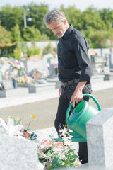 mature handsome man watering flowers at the cemetery