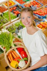 Lady holding wicker basket of vegetables