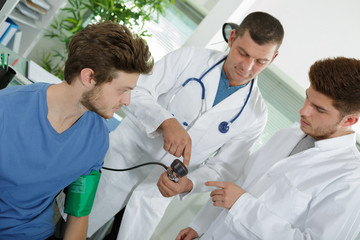 doctor is measuring the blood pressure of an young patient