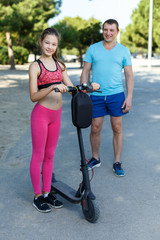 Girl riding kick scooter with father