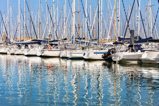 Reflections of colourful sailing boat masts on water