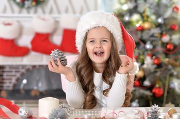 Portrait of happy little girl in Santa hat