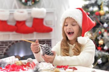 Portrait of cute little girl in Santa hat preparing for Christmas