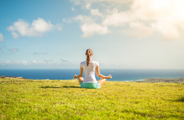 young woman meditating in a grass field
