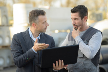 manager and worker talking outside and using a laptop