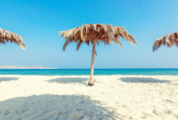 Fototapete - Beautiful landscape, tropical beach with white sand and umbrellas of palm leaves, calm down and travel, minimalistic concept