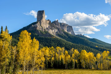 Chimney Peak - Evening view of Chimney Peak rock formations, 11,781 ft (3,591 m), surrounded by golden autumn aspen trees, near the summit of Owl Creek Pass, 10,114 ft (3,083m). Colorado, USA. Wall mural