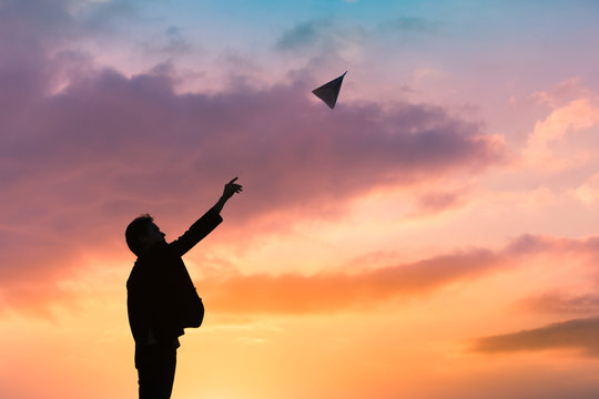 Silhouette of man throwing paper airplane. Creativity, inspiration, imagination concepts