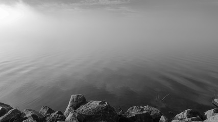 Thick fog on lake. Monochrome misty water. Rocks in foreground.