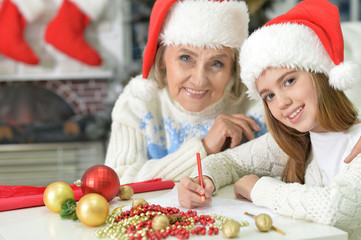 Portrait of grandmother with teen girl in Santa hats preparing for Christmas at home