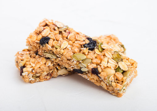 Homemade organic granola cereal bars with nuts and dried fruit on white background