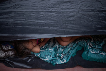 A girl sleeps under a tarp amid thousands of other migrants from Central America en route to the United States in Huixtla, Mexico