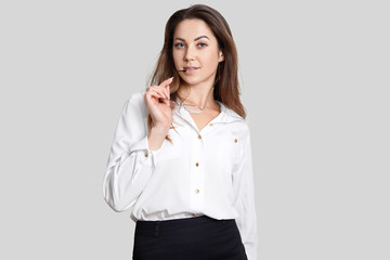 Self confident female model keeps spectacles in hands, wears white blouse and blak skirt, looks with serious expression directly at camera, isolated over white background. People and business concept
