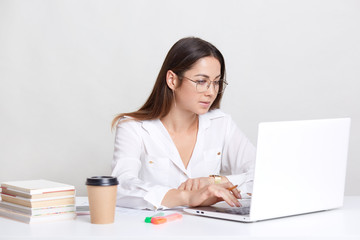 Young female administrative works on laptop computer, searches information in internet, dressed in white drinks hot beverage, uses books for writing diploma paper, isolated over white background