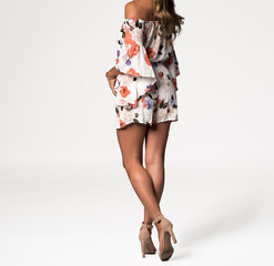 Beautiful Woman with Her Back Turned in a Short Floral Print Romper Suit
