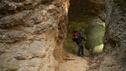 Wall Mural - Small Cave Exploring by Caucasian Hiker in His 30s.