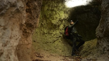Wall Mural - Caucasian Men in His 30s with Flashlight Exploring Grotto. Geological Researcher.