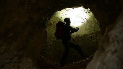 Wall Mural - Rescuer with Flashlight Looking Around in the Deep Cave. Rescue Mission.