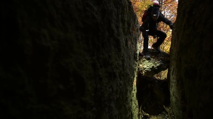 Wall Mural - Hiker with Flashlight Exploring New Cave Entrance. Scenic Fall Foliage in the Background