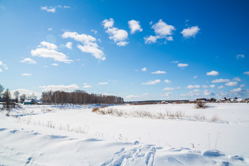 Winter landscape. Countryside. Frozen river. Sunny day. Blue sky. White clouds.