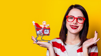 Portrait of a young woman in glasses with shopping cart full of christmas gifts on yellow background