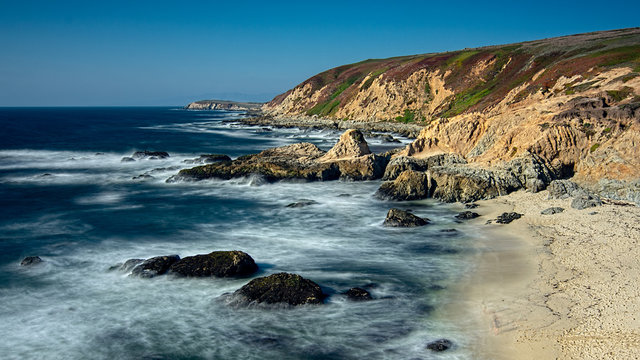 Landscape view of Bodega Bay beach in Sonoma County in California, USA, on a typical summer day in the morning, featuring blue water and blue sky