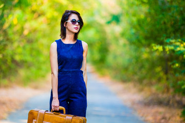 portrait of the beautiful young woman with suitcase standing in the middle of the road