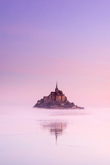 old castle in foggy morning between sky and water in France