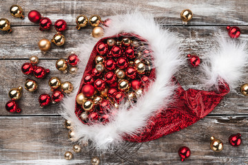 Old wooden Christmas background, Santa Claus hat full of baubles. Top view. Space for text.