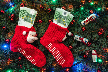 Background of fir branches. Santa's red stockings with money. Christmas card. Top view. Xmas congratulations. Lights