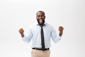 Happy african businessman wearing a corporate grey shirt and black tie punching the air with his fists arms in air, smiling and shouting in victorious success for his business deal