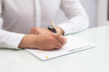 Close-up of businessman sitting at table and writing on paper. Young Caucasian manager working in office. Marketing concept