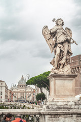 Statue near the castle of the Holy Angel. View of the Vatican and St. Peter's. Rome, Italy
