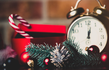 Christmas decoration with retro alarm clock, Santa Claus hat, baubles and pine cone with branch on brick wall background