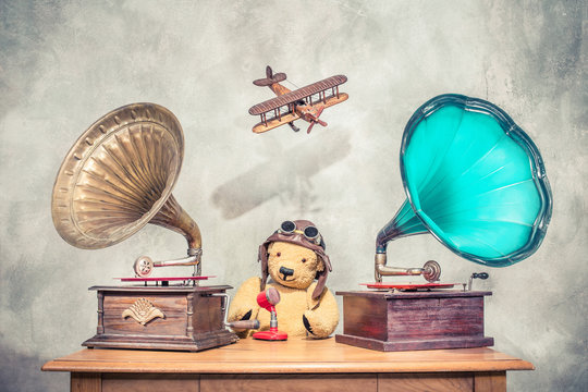 Teddy Bear with aviator's helmet and goggles, aged antique gramophone phonograph turntables with old retro microphone, flying toy plane with its shadow on concrete wall. Vintage style filtered photo