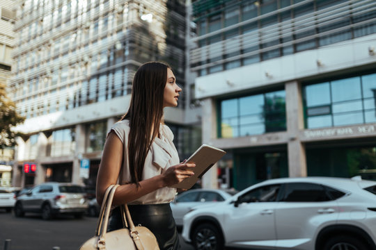 Young business lady catches a taxi at work
