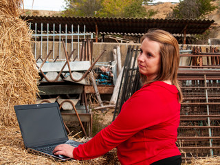 An entrepreneur young woman working outdoor on a farm with a laptop over a hay bale