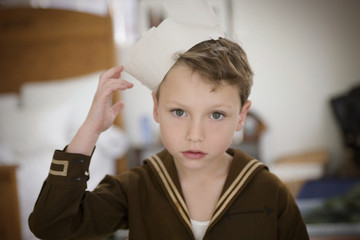 Portrait of a young boy wearing a sailors hat.
